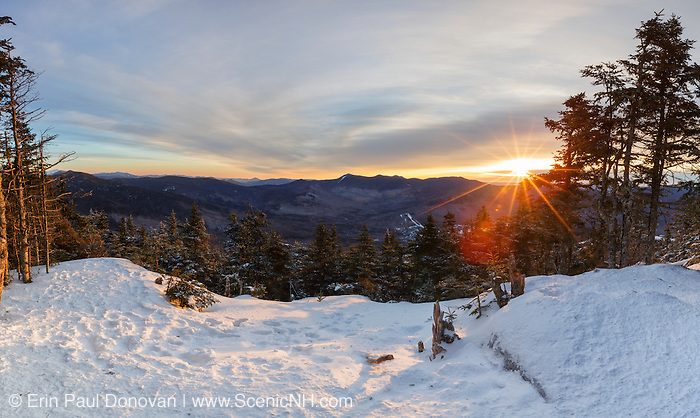 Scenic view from the summit of Mt Tecumseh in Waterville Valley, New Hampshire at sunrise during the winter months. This image consists of three images stitched together. Illegal tree cutting (vandalism) over the last few years has improved the view from this spot on the summit.