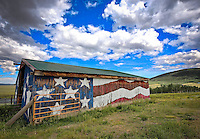 Rustic barn with American flag painted on it.
