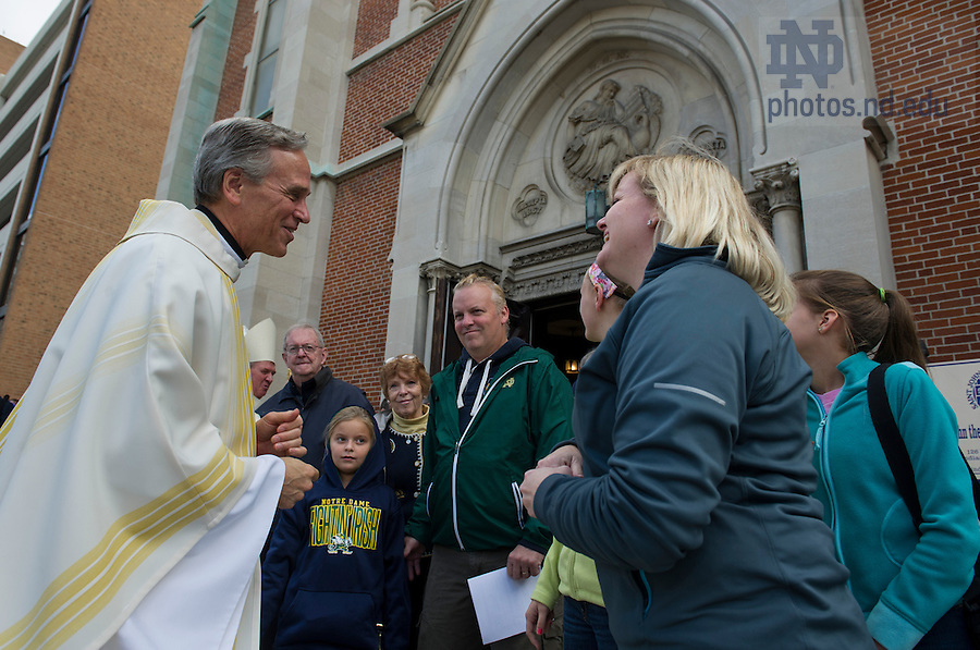 Sept 13, 2014; Notre Dame president Rev. John Jenkins, C.S.C., shakes hands after celebrating Mass at Saint John the Evangelist Catholic Church before the Shamrock Series football game in Indianapolis. (Photo by Barbara Johnston/University of Notre Dame