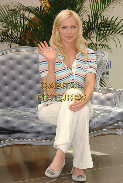 """LAURA PREPON .attends a photocall promoting the television series """"October Road"""" on the third day of the 2008 Monte Carlo Television Festival held at Grimaldi Forum in Monte Carlo, Principality of Monaco, .June 10, 2008..full length sitting striped top cream trousers legs crossed hand waving.CAP/TTL .©TTL/Capital Pictures"""