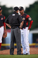 Batavia Muckdogs manager Angel Espada (4) argues a call with umpire John Budka during a game against the State College Spikes on June 23, 2016 at Dwyer Stadium in Batavia, New York.  State College defeated Batavia 8-4.  (Mike Janes/Four Seam Images)