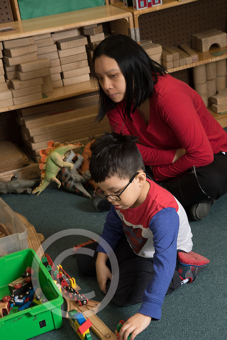 Education Preschool therapist observing and working with boy in classroom as he plays with train set