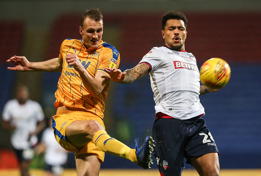 Bolton Wanderers' Josh Magennis competing with Wigan Athletic's Dan Burn<br /> <br /> Photographer Andrew Kearns/CameraSport<br /> <br /> The EFL Sky Bet Championship - Bolton Wanderers v Wigan Athletic - Saturday 1st December 2018 - University of Bolton Stadium - Bolton<br /> <br /> World Copyright © 2018 CameraSport. All rights reserved. 43 Linden Ave. Countesthorpe. Leicester. England. LE8 5PG - Tel: +44 (0) 116 277 4147 - admin@camerasport.com - www.camerasport.com