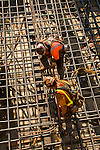 Construction workers tieing rebar at the base of a platform for a bridge tower.
