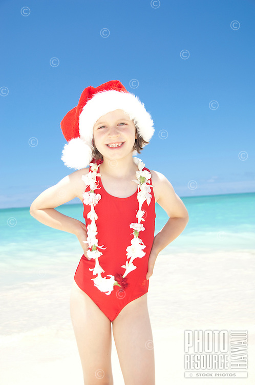 Young girl on white sand beach in red swimsuit and Santa hat and lei to celebrate Christmas in Hawaii.