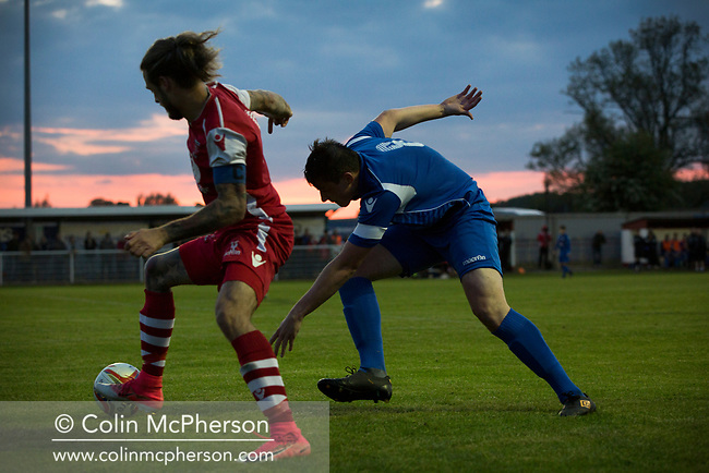 Two players competing for the ball during the second-half action at Yockings Park as Whitchurch Alport (in red) hosted Cammell Laird 1907 in the 2017-18 North West Counties Division One play-off final. Alport were formed in 1946 and were named after Alport Farm, Whitchurch, which had been the home of a local footballer Coley Maddocks who had been killed in action in the war. The home team won the match 2-1 watched by a crowd of 773, a club record attendance.