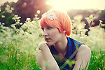 Young girl with orange hair and blue top looking away, in a field of flowers, with sunset light.