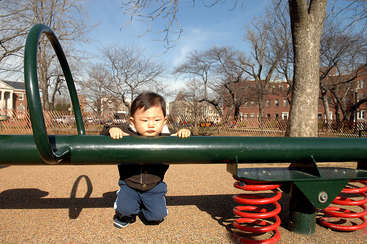 Fifteen month old Nathan Wood rests on a seesaw in Stanton Park.