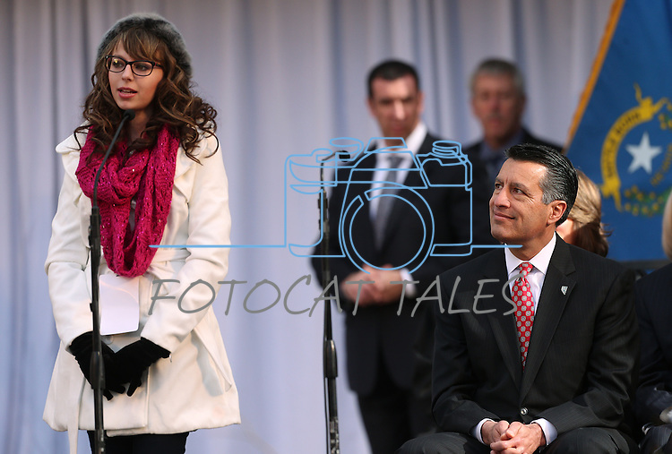 Gov. Brian Sandoval, right, listens as Melanie Anderson, of Elko County, sings at the inauguration at the Capitol, in Carson City, Nev., on Monday, Jan. 5, 2015.<br /> Photo by Cathleen Allison