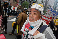A demo march by left wing groups and anti-nuclear campaigners passes protesting right-wing uyoku dantai sound trucks in Ginza, Tokyo, Japan Sunday November 6th 2011