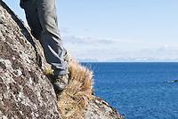 feet of person hiking along rocks near coast, Lofoten, Norway