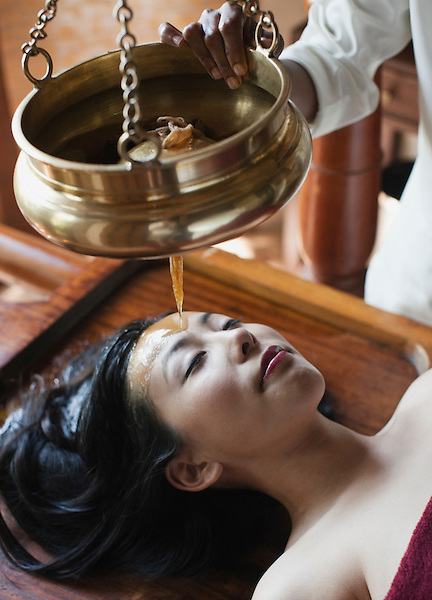 Woman Receives Shirodhara Ayurvedic Treatment in the Sariva Room at Ananda Spa, Ananda in the Himalayas, The Palace Estate, Narendra Nagar, Tehri Garhwal, Uttarakhand, India. Shirodhara involves the gentle pouring of warm oil over the forehead. This ancient restrative practice has been used to treat a variety of ailments, including: eye diseases, sinusitis, allergies, greying of hair, neurological disorders, memory loss, insomnia, hearing impairment, and vertigo.