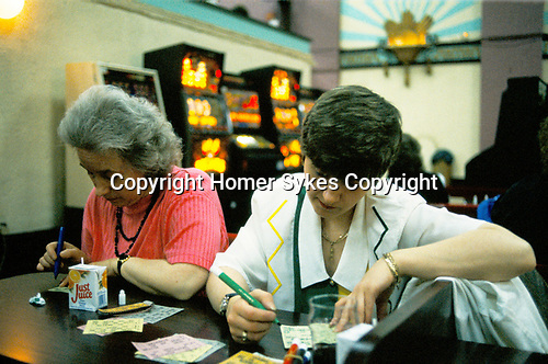 Bingo UK two women  playing Bingo Club drinking Just Juice in a paper carton, north London. 1990s 90s