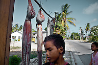Frederick Cannon, who competed in running internationally...Fred, a known spear fisherman, who believes in transmitting the knowledge of hunting in the sea to his kids. In front of his hosue, octopus etc that he recently fished are for sell...Nauru, officially the Republic of Nauru is an island nation in Micronesia in the South Pacific.  Nauru was declared independent in 1968 and it is the world's smallest independent republic, covering just 21 square kilometers..Nauru is a phosphate rock island and its economy depends almost entirely on the phosphate deposits that originate from the droppings of sea birds. Following its exploitation it briefly boasted the highest per-capita income enjoyed by any sovereign state in the world during the late 1960s and early 1970s..In the 1990s, when the phosphate reserves were partly exhausted the government resorted to unusual measures. Nauru briefly became a tax haven and illegal money laundering centre. From 2001 to 2008, it accepted aid from the Australian government in exchange for housing a Nauru detention centre, with refugees from various countries including Afghanistan and Iraq..Most necessities are imported on the island..Nauru has parliamentary system of government. It had 17 changes of administration between 1989 and 2003. In December 2007, former weight lifting medallist Marcus Stephen became the President.