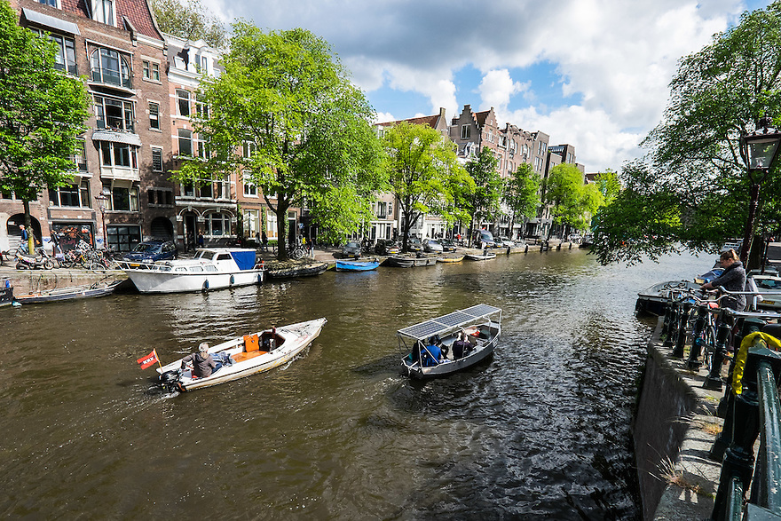 Nederland, Amsterdam, 30 mei 2015<br /> Amsterdamse grachten met electrisch verhuurbootje met zonnepanelen op het dak van het bootje. <br /> Foto: Michiel Wijnbergh