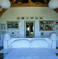 View over the bed located in the centre of the bedroom towards the open door and a wall covered in framed prints and paintings