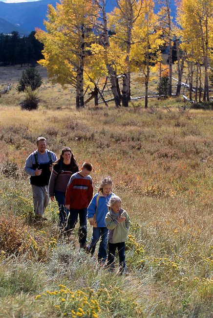 A family of five hiking on a meadow trail in single file during fall in Rocky Mtn Nat'l Park, CO.