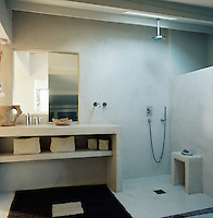 A concrete wet room with a mirror above a shelving unit and an open shower area.