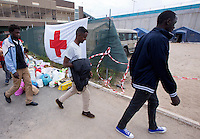 Migranti entrano nella tendopoli allestita presso la stazione Tiburtina a Roma, 16 giugno 2015.<br />