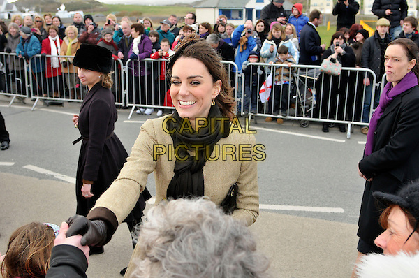 KATE MIDDLETON.Launch the new Hereford Endeavour lifeboat, Trearddur Bay Lifeboat Station, Holyhead, Isle of Anglesey.Launch of the new Hereford Endeavour lifeboat, Trearddur Bay Lifeboat Station at Anglesey,Trearddur, Wales..February 24th, 2011.royal royals royalty half length black scarf beige hair accessory feathers  gloves shaking hands meeting fans crowd audience .CAP/CAS.©Bob Cass/Capital Pictures.