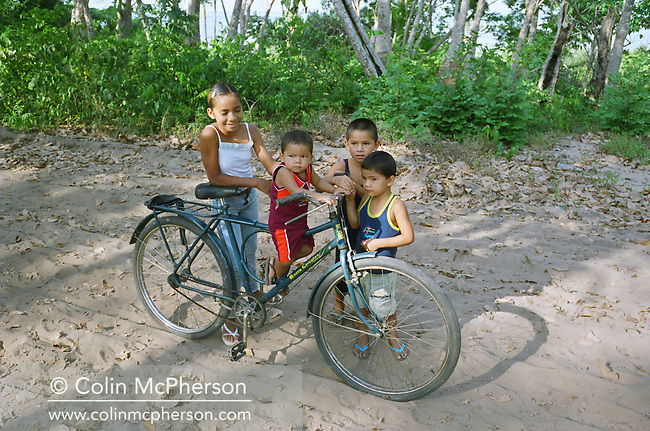 Children with a bicycle making their way to primary school in the village of Jaguarari in the Amazon. The Floresta Nacional do Tapajos (FLONA), a 6500 km2 protected reserve, was home to several small communities which lived on the banks of the Rio Tapajos river. The communities did not have electricity or running water and access to the villages was by unpaved dirt roads from Santarem and Highway BR163.