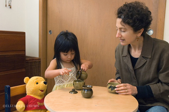 Berkeley CA Girl, two and a half, Guatemalan, and adoptive mother having tea party together with Pooh  MR