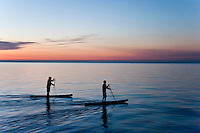 A pair of stand up paddleboard paddlers silhouetted during an evening workout on Lake Superior at Grand Marais Michigan.
