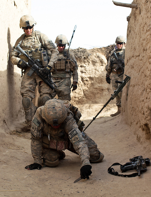 Sgt. James Leatherwood, 25, of Dublin, Texas, a soldier with Company B, 2nd Battalion, 508th Parachute Infantry Regiment, probes the ground after picking up a metallic signature on his mine detector in the village of Deh-e-Chowkay, in the Arghandab valley near Kandahar, Afghanistan. It turned out to be a false alaram. May 22, 2010. DREW BROWN/STARS AND STRIPES