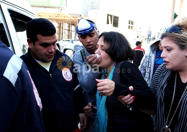 A Palestinian woman is being helped next to the checkpoint of Kalandia, West Bank, 08 March 2012, North of Jerusalem, victim of the clashes between protesters and Israely soldiers during a rally to mark the International Women's Day.  Photo by Issam Rimawi