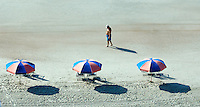 A man walks past beach umbrellas for rent in front of a hotel at Virginia Beach, Va.