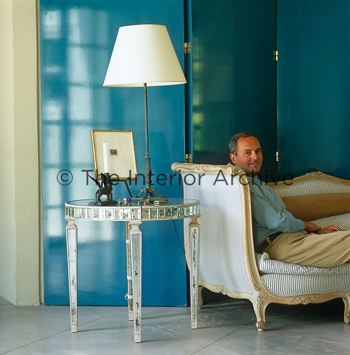 John Stedila relaxes in his living room on an antique sofa arranged in front of a large contemporary folding screen of his own design constructed from panels lacquered a deep turquoise