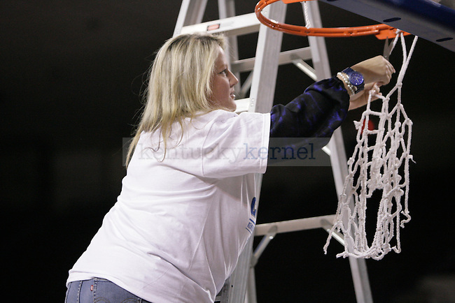 Associate Media Relations Director and Women's Basketball SID, Susan Lax, cuts down a piece of the net during the Kentucky Women's celebration of winning the SEC regular season championship 2/26/12 at Memorial Coliseum in Lexington, Ky. Photo by Quianna Lige | Staff