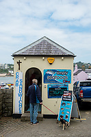 A man stands in the doorway of a seafood shop at Tenby, Pembrokeshire, Wales, UK