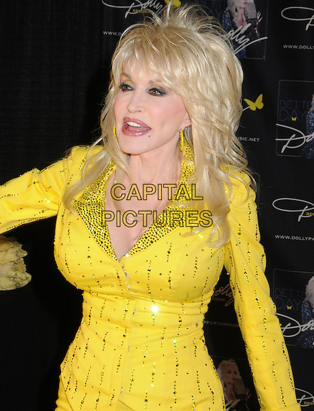 Dolly Parton signs autographs for a limited number of lucky fan winners during the 2011 CMA Music Festival at Fan Fair Exhibit Hall at the Nashvile Convention Center, marking her first autograph session at the event since the mid-'70s. Nashville, Tennessee, USA 11th June 2011.half length yellow dress gold mouth open jacket beads beaded.CAP/ADM/LF.©Laura Farr/AdMedia/Capital Pictures.