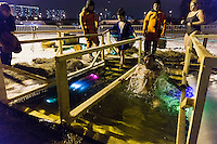 Moscow, Russia, 18/01/2016.<br /> A young women enters the water as a man emerges as Orthodox Christian believers celebrate Epiphany at a lake in southern Moscow. Priests blessed the waters and followers baptised themselves by total immersion in the freezing lake in temperatures of minus 11C.