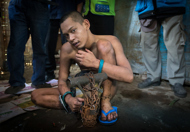 "5 April 2017, Surabaya,East Java,Indonesia: Febrianto, a 24 year old mental illness sufferer prepares to be released from the chains he has been shackled to a stake for the past two years in a goat shed next to his family in Pehwetan village, East Java. Indonesian Social Affairs Dept. workers cut the bonds and wash his emaciated body and apply first aid before putting him in a straight jacket and taking him to a facility in Malang for treatment. Febrianto is a patient in a program called ""E- Shackling"" which aims to free people suffering from mental illness, from the shackles that family often place them in to control them in the wake of a lack of treatment options and which will treat them and enter them in a data base allowing them to be traced before releasing them back to their families. Some people stay chained to a stake or in rooms for years by their families and not all families are willing to take their sick family members back. Picture by Graham Crouch/The Australian"