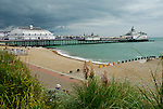 View of Eastbourne Pier and beach in sunshine with dramatic storm clouds overhead, East Sussex, England