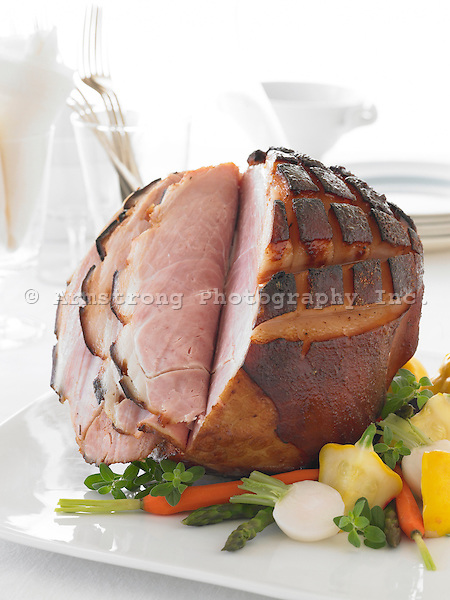 A baked ham with vegetables on a white tablecloth. Napkins, plates, forks, and glasses in background