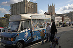 Family buying ice creams from van with Abbey Great Gate and cathedral behind, Bury St Edmunds, Suffolk, England