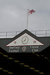Sheffield United 2 Leeds United 0, 19/03/2011. Bramall Lane, Championship. The stadium clock and flag on the roof of the John Street Stand at Sheffield United's Bramall Lane ground prior to the Npower Championship fixture against Leeds United. The home team won the game by two goals to nil watched by a crowd of 23,728. Bramall Lane is the world's oldest professional football ground and at one time hosted both football and cricket. Photo by Colin McPherson.