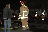 Sunday, June 20, 2010:  Steve Ferguson speaks with a San Diego Firefighter from Station 13 as other firefighters remove charred possesions from his vehicle on the corner of Opal and Dawes at approximately 9pm Sunday night.  Ferguson, who has lived in the van for the past couple of years escaped the fire unharmed but most of his possesions and the vehicle were a complete loss.  He believes that the cause of the fire was a battery short in the engine compartment.