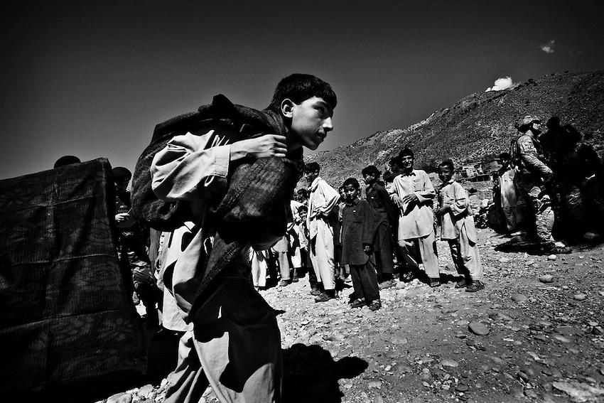 The Afghan National Army hands out humanitarian aid under supervision of the US Marines and US Army in the village of Tarale in the Pesh Valley, Kunar Province, Afghanistan, Monday, Sept 28, 2009. The humanitarian aid was handed out with the cooperation of village elders who designated the poorest families in the village to give the majority of the aid to. Items given included palm oil, tea, radios, blankets, children's clothing, flour and rice.
