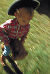 young boy with cowboy hat riding toy horse