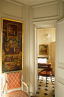 A gilt-framed Renaissance painting hangs above a bergere in the hallway