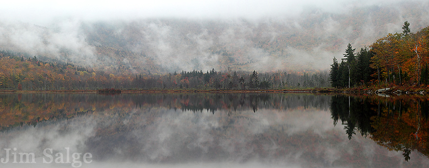Low clouds hang over Basin Pond, with muted autumn colors along the shore.