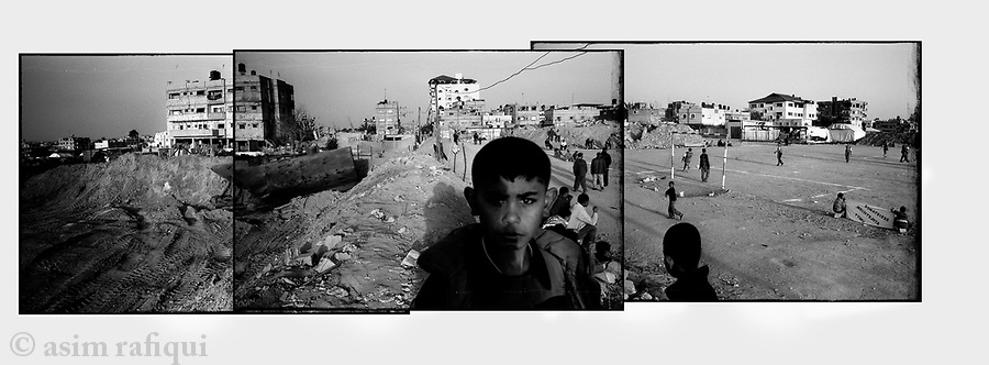 Location: The Egyptian-Gaza border, Rafah, Gaza..Young Palestinian boys watch the first football game in the city since the declaration of the ceasefire...The game, being played along the heavily bombarded, Egyptian-Rafah border area, was meant to raise awareness of the struggles and suffering of Rafah's children...The infamous Gaza tunnels are mosly built along this area and were the stated reasons for the heavy bombardment.