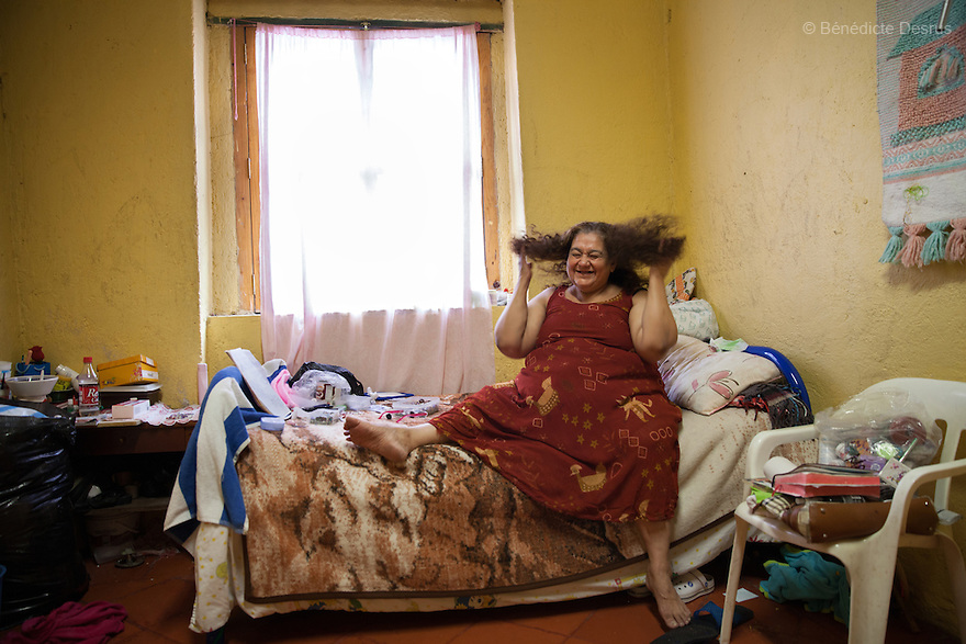 "María Isabel, a resident of Casa Xochiquetzal, in her bedroom at the shelter in Mexico City, Mexico on July 8, 2013. María Isabel, who grew up in Michoacán, Mexico, ran away from home at the age of 9 after a year in which her father ""used her."" When she got to the Mexico City bus station, she met a woman selling tamales who offered her a home and education. María Isabel nearly finished her studies to become a teacher, but when her caretaker died, she became a sex worker at 17. She now reads, writes poetry, embroiders, and makes earrings and bracelets. Casa Xochiquetzal is a shelter for elderly sex workers in Mexico City. It gives the women refuge, food, health services, a space to learn about their human rights and courses to help them rediscover their self-confidence and deal with traumatic aspects of their lives. Casa Xochiquetzal provides a space to age with dignity for a group of vulnerable women who are often invisible to society at large. It is the only such shelter existing in Latin America. Photo by Bénédicte Desrus"