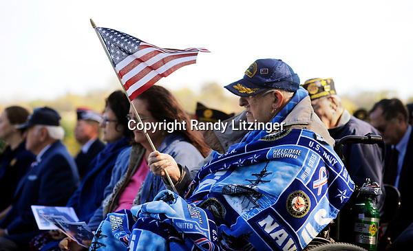 91-year-old WWII and Korean War veteran Gideon Gilliam holds an American Flag during the Veteran's Day celebration on hospital hill in Warrenton Friday morning. Gilliam served in the Navy during WWII aboard the USS Massachusettes, USS Wisconsin, and the USS Caloosahatchee. He also served in the Navy during the Korean War.<br />