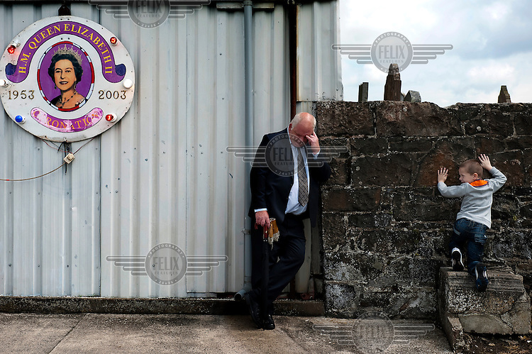 A protestant man and boy at Drumcree church, Belfast, during the annual Orange parade. To the left a sign celebrates Queen Elizabeth II....