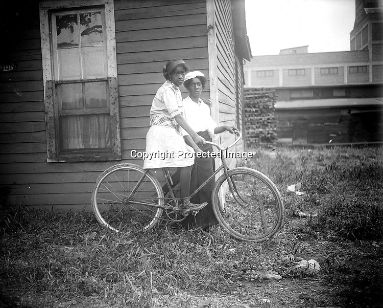 FLORENCE JONES AND HER MOTHER. Florence and her mother, Kate (Constellawaii) Wilson (1883-1962), lived on South Seventh Street, at the edge of an industrial area. The building in the background was the Griswold Seed Company elevator at Eighth and N Streets. Ruth Folley recalled Florence bicycling all over Lincoln. They once rode together to Florence's dish-washing job at a big house on Sheridan Boulevard. Florence graduated from Lincoln High School in 1923.<br /> <br /> Photographs taken on black and white glass negatives by African American photographer(s) John Johnson and Earl McWilliams from 1910 to 1925 in Lincoln, Nebraska. Douglas Keister has 280 5x7 glass negatives taken by these photographers. Larger scans available on request.